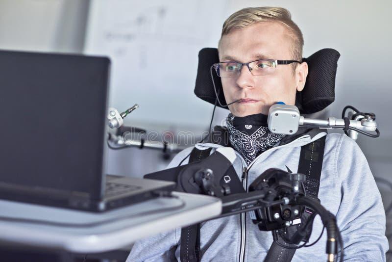 Behinderter Student, der mit seinem Computer arbeitet stockbilder
