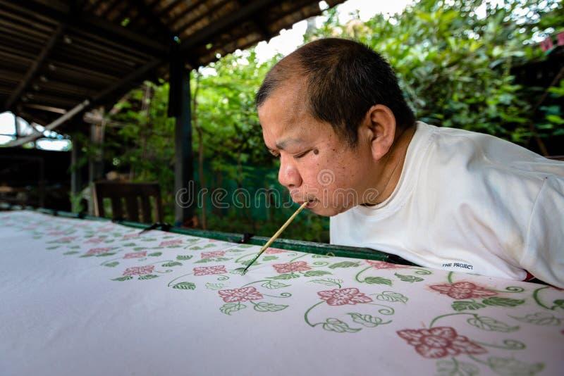 Behinderter thailändischer Mann malt Batikgewebemuster mit seinem Mund lizenzfreie stockfotografie