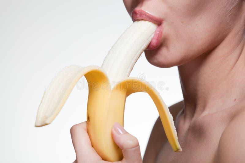 Beißende Banane der jungen Frau getrennt auf Weiß lizenzfreies stockfoto