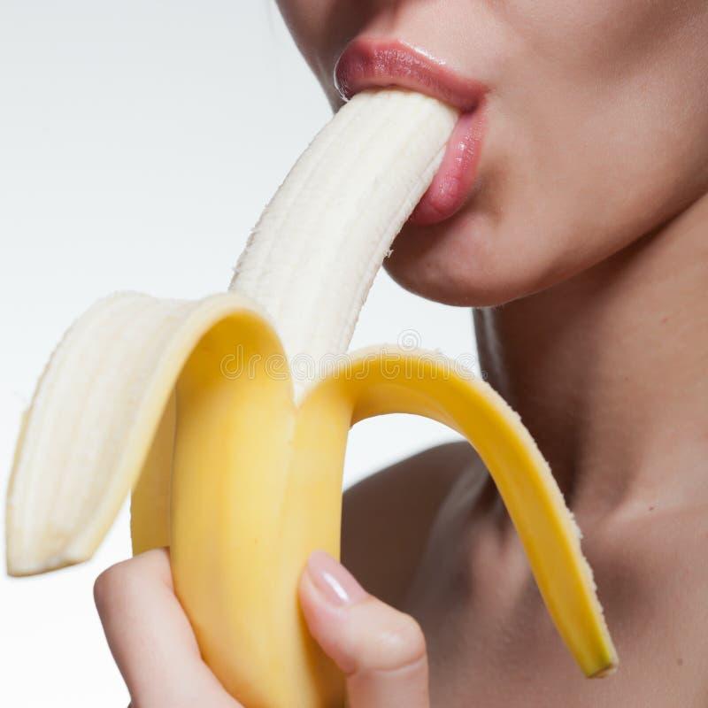 Beißende Banane der jungen Frau lokalisiert auf Weiß stockfotografie