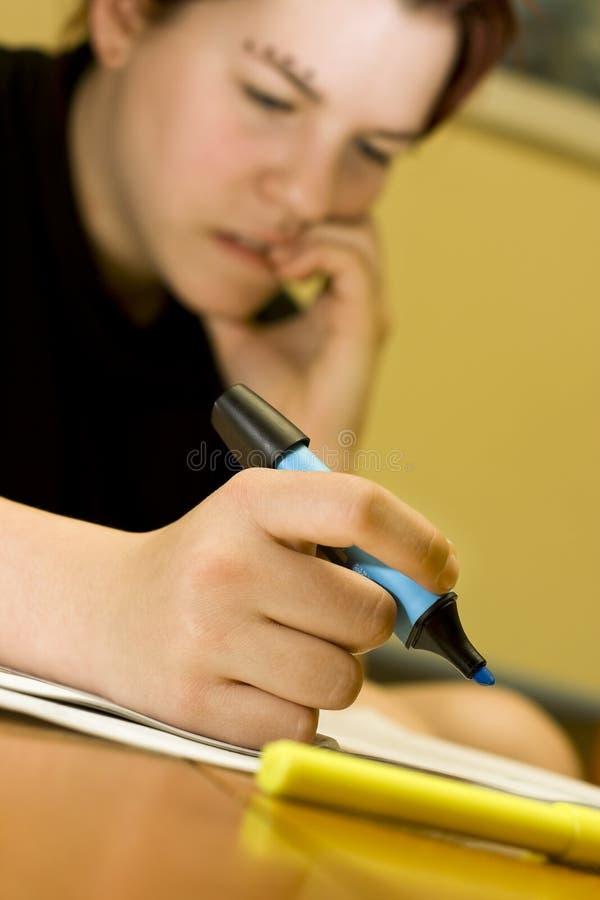 Beißende Nägel des Studentenmädchens beim Studieren stockfoto