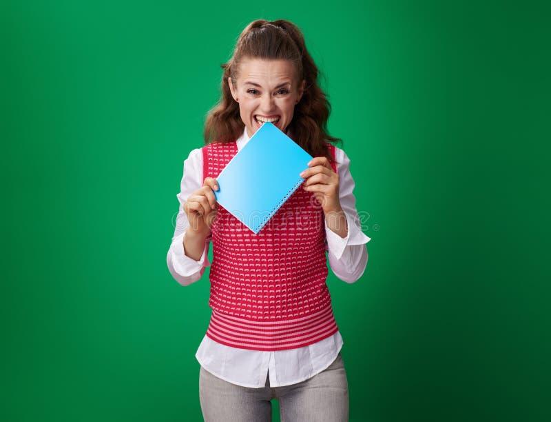 Beißendes blaues Notizbuch der Studentenfrau lokalisiert auf grünem Hintergrund lizenzfreie stockbilder