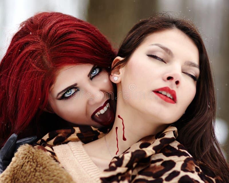 Beißendes unschuldiges Mädchen des Redheaded Vampirs stockfoto