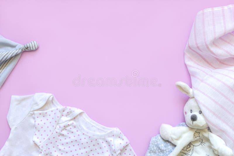 Bei accessori stabiliti del bambino - piccolo cappello, vestiti del neonato e giocattoli divertenti su fondo rosa copi lo spazio, fotografia stock