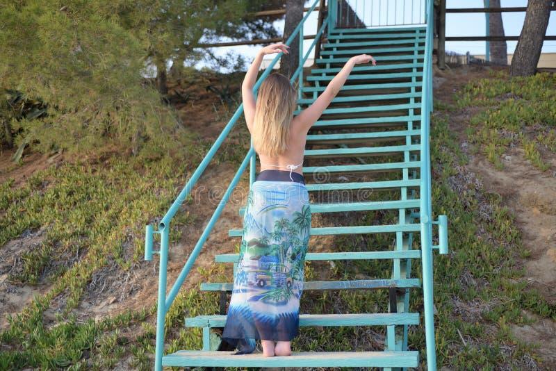 Bei balli biondi della ragazza lentamente sulle scale di nuovo alla macchina fotografica con le armi alzate immagini stock