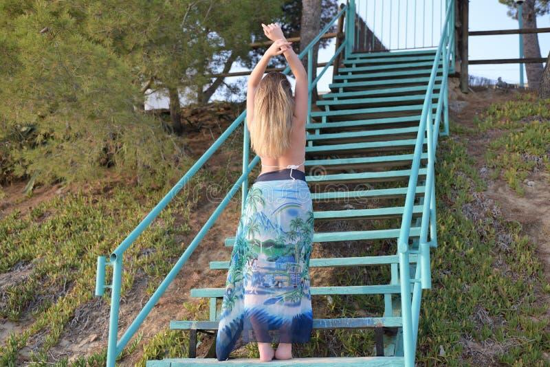 Bei balli della ragazza sulle scale di nuovo alla macchina fotografica fotografia stock libera da diritti