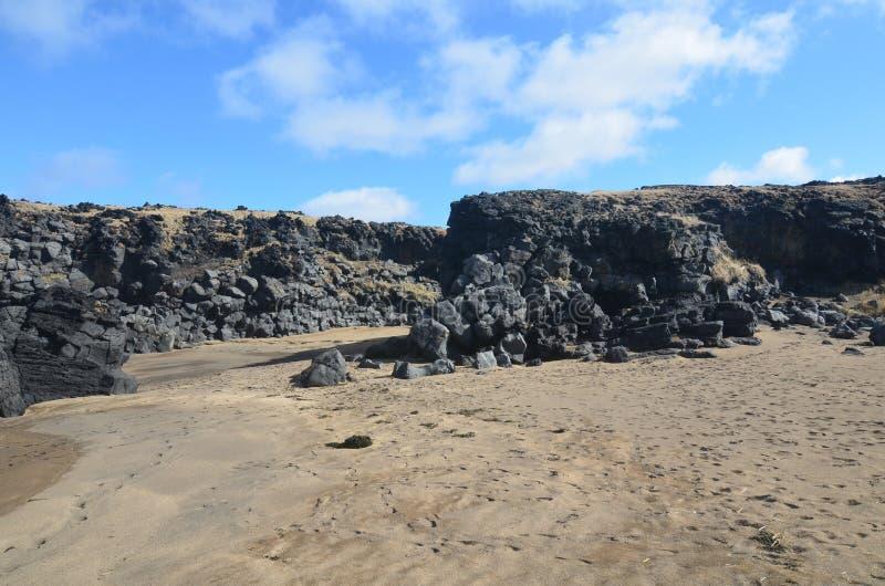 Bei cieli blu sopra una grande formazione rocciosa in Islanda fotografie stock