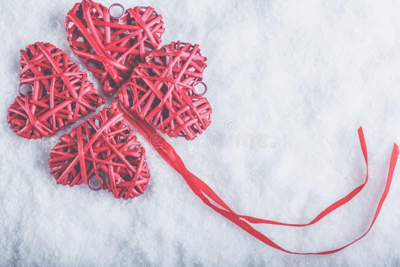 Bei cuori rossi d'annata romantici insieme su un fondo bianco della neve Amore e concetto di giorno di biglietti di S. Valentino  fotografia stock libera da diritti