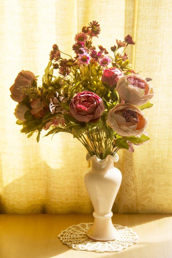 Bei fiori artificiali delle peonie e dei crisantemi in un vaso rosa delicato su un fondo giallo ocraceo caldo fotografia stock