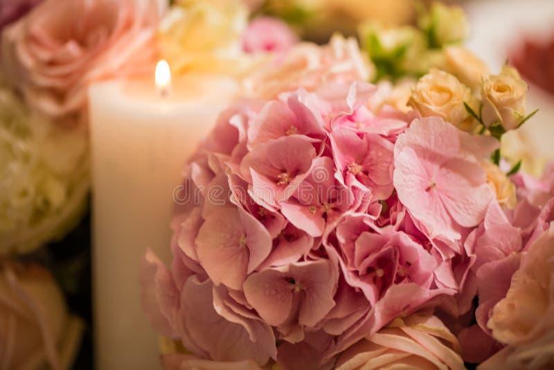 Bei fiori dei colori e delle candele differenti sulla tavola immagini stock libere da diritti