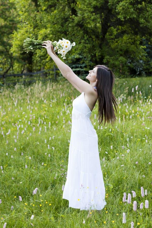 Bei fiori della holding della ragazza in un prato fotografia stock libera da diritti