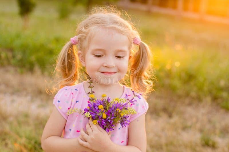 Bei fiori di raccolto della bambina in un prato fotografie stock