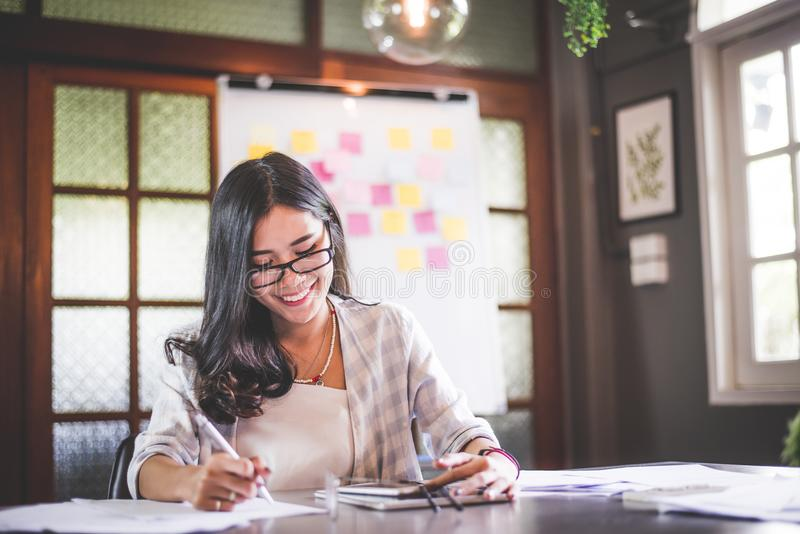 Bei funzionamento della donna di affari e nota asiatici di scrittura immagini stock