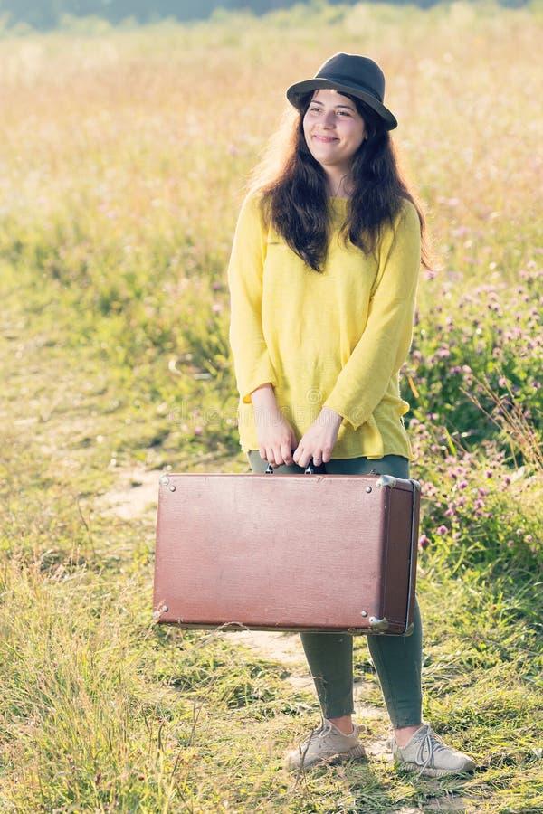 Bei giovane donna sorridente felice con la valigia d'annata marrone e black hat nella strada del campo immagine stock libera da diritti