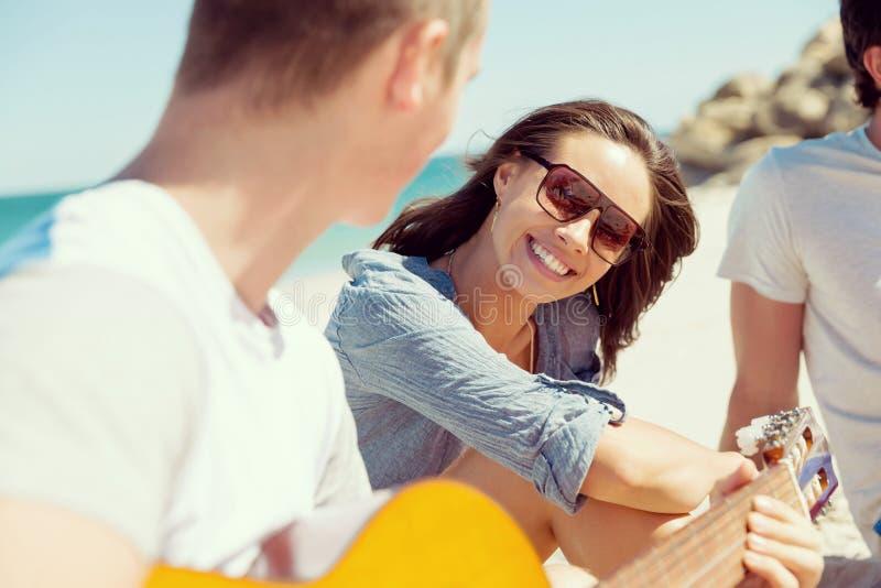 Bei giovani con la chitarra sulla spiaggia fotografie stock