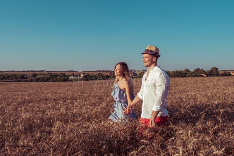 Bei giovani coppie, uomo e donna, giacimento di grano di camminata di estate, tenendo mano di ciascuno, sorridere felice romantic immagine stock libera da diritti
