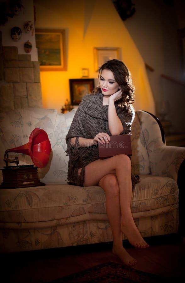 Bei giovani piedi nudi di donna che si siede sul sofà che tiene un libro che ha un grammofono rosso vicino lei, paesaggio d'annat immagine stock libera da diritti