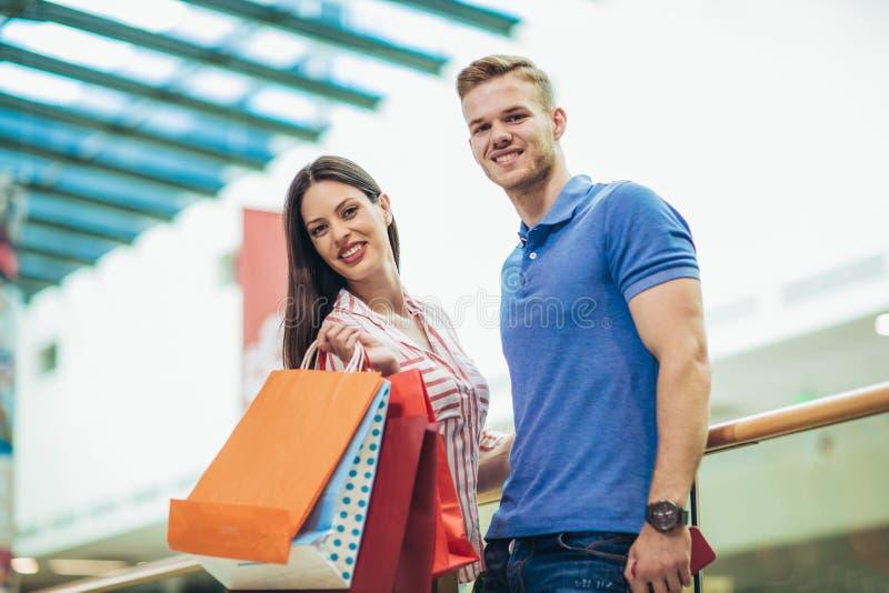 Bei giovani sacchetti della spesa felici e sorridere della tenuta delle coppie fotografia stock