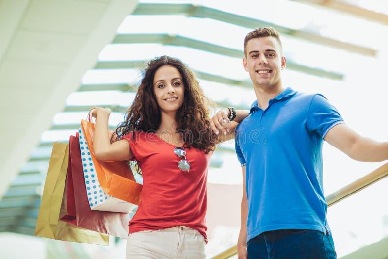 Bei giovani sacchetti della spesa felici e sorridere della tenuta delle coppie fotografie stock libere da diritti