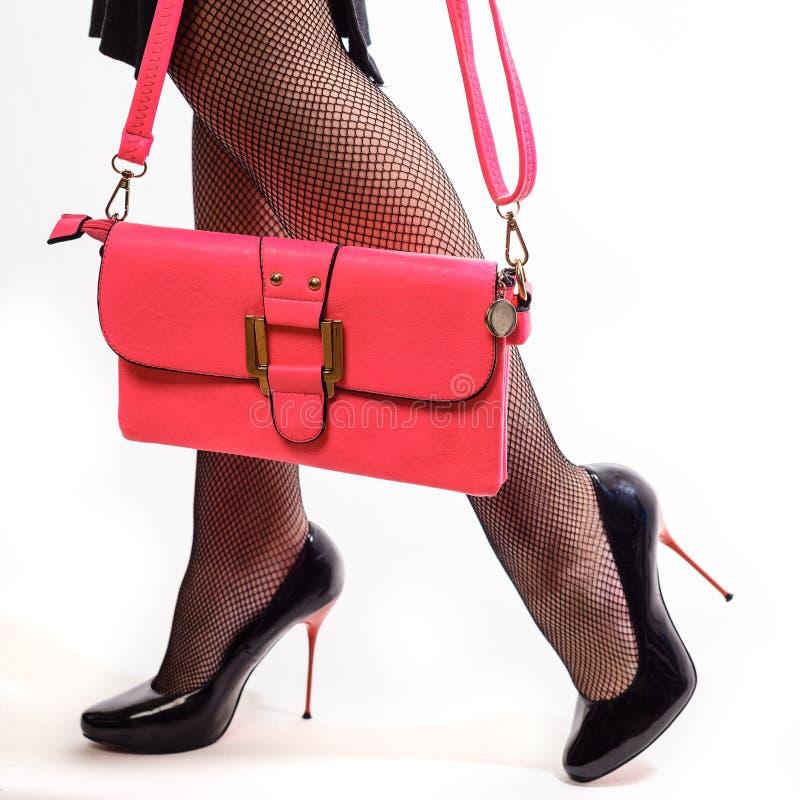 Bei inshoes femminili delle gambe sugli stiletti rossi e sulle frizioni rosa fotografia stock libera da diritti