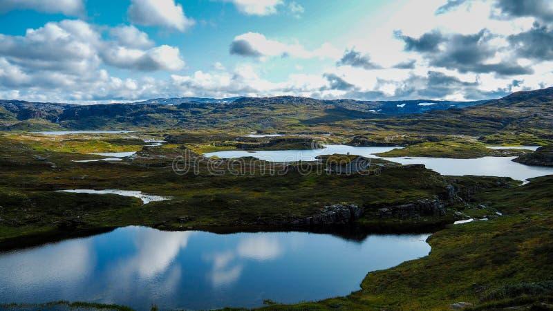 Bei laghi blu del ghiacciaio che riflettono il cielo in parco nazionale norvegese immagine stock libera da diritti