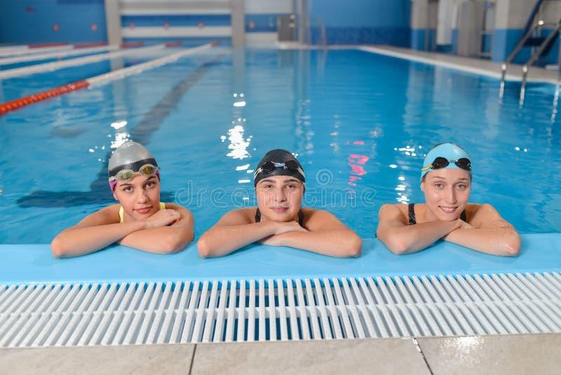 Bei nuotatori femminili che sorridono alla macchina fotografica nella piscina immagine stock libera da diritti