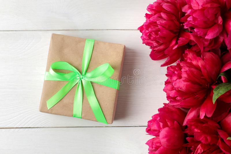 Bei peonie dei fiori e contenitore di regalo rosa luminosi su un fondo di legno bianco Vista superiore immagine stock libera da diritti