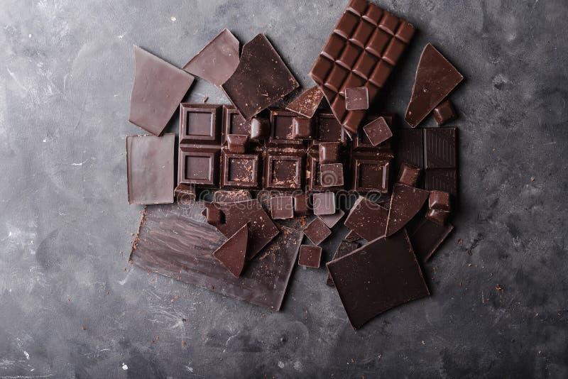 Bei pezzi del cioccolato Pezzi di Antivari di cioccolato Una grande barra di cioccolato su fondo astratto grigio immagini stock libere da diritti