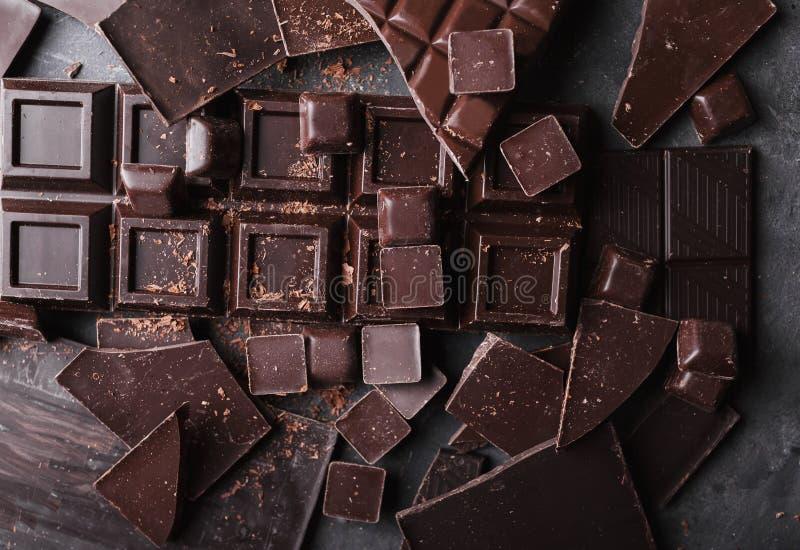 Bei pezzi del cioccolato Pezzi di Antivari di cioccolato Una grande barra di cioccolato su fondo astratto grigio fotografia stock