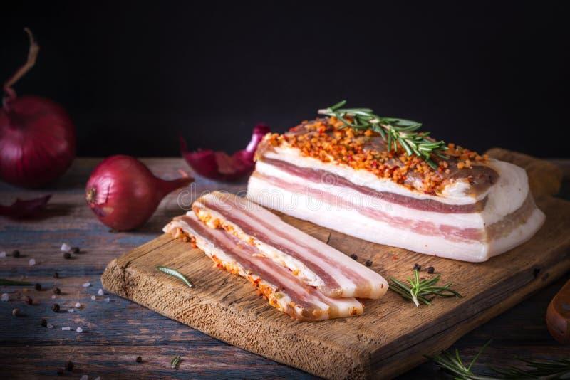Bei pezzi di bacon salato su fondo scuro E r immagini stock