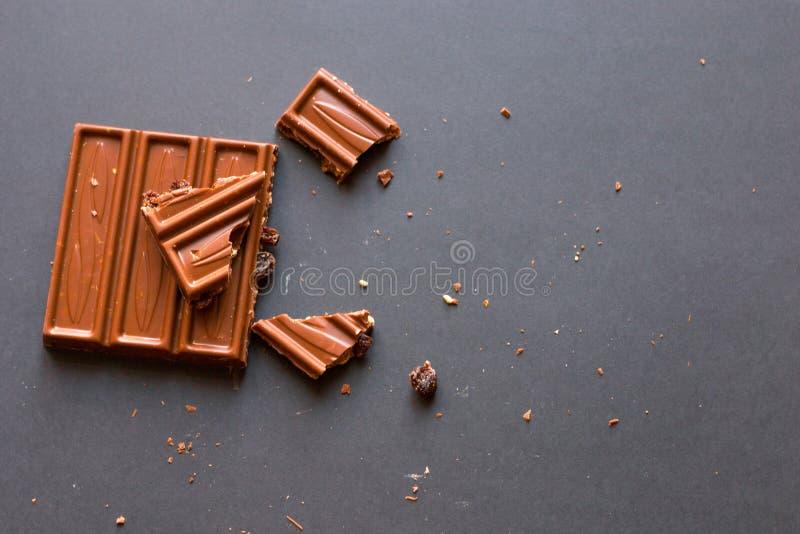 Bei pezzi di cioccolato al latte con le nocciole e l'uva passa schiacciate con alcool su fondo nero Degustation della confetteria fotografia stock libera da diritti