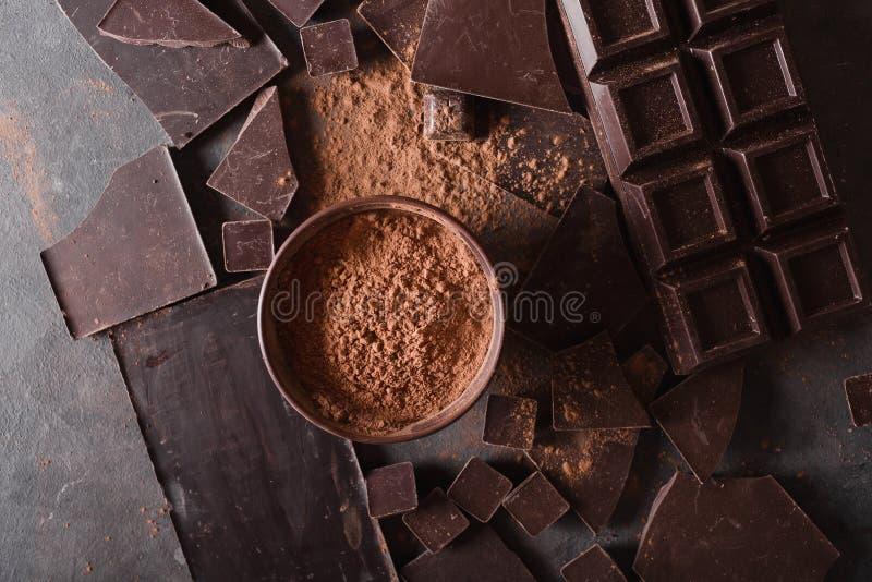 Bei pezzi e cacao in polvere del cioccolato Pezzi di Antivari di cioccolato Una grande barra di cioccolato su fondo astratto grig immagini stock libere da diritti