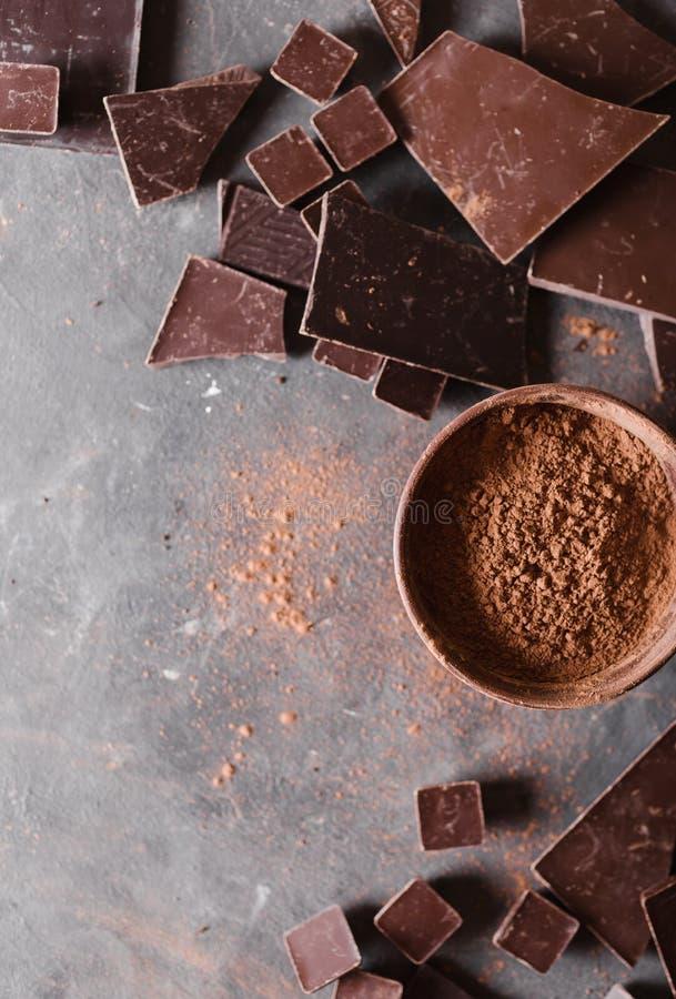 Bei pezzi e cacao in polvere del cioccolato Pezzi di Antivari di cioccolato Una grande barra di cioccolato su fondo astratto grig fotografia stock