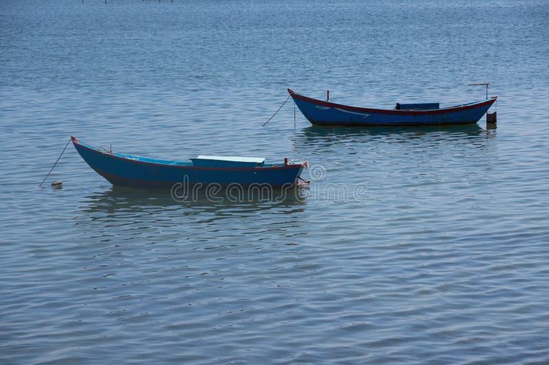 Bei piccoli pescherecci ed uomo del pescatore sul mare con il fondo del cielo blu e la parte 2 della baia di Sud-est asiatico immagini stock
