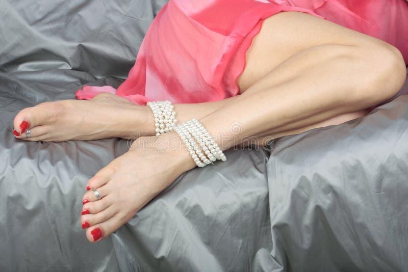 Bei piedini della donna sopra il tessuto del raso immagine stock libera da diritti