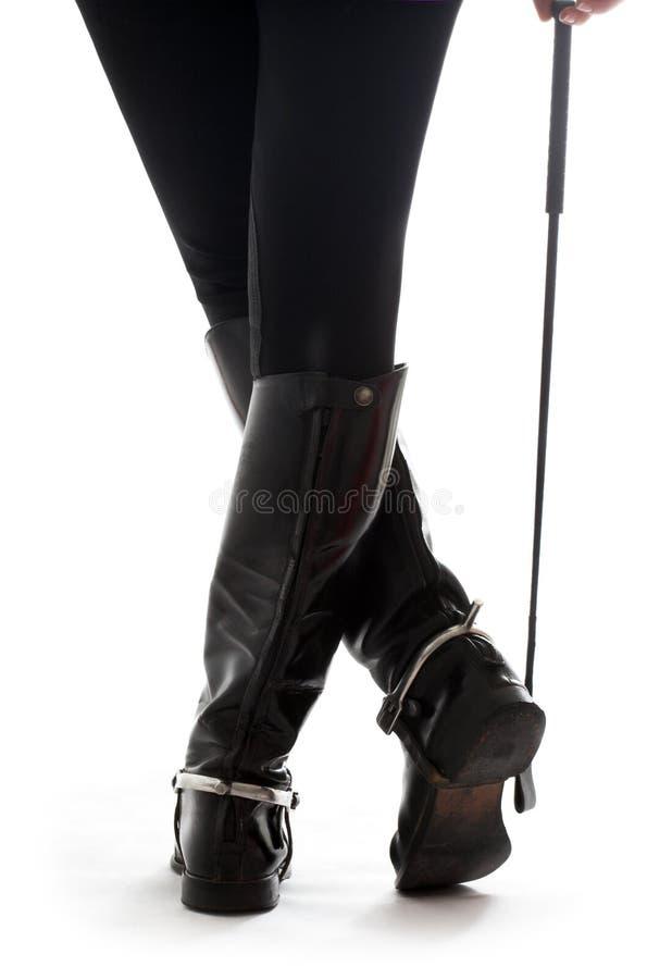 Bei piedini nei caricamenti del sistema di cuoio neri del cavallerizzo con il riding-crop fotografie stock libere da diritti