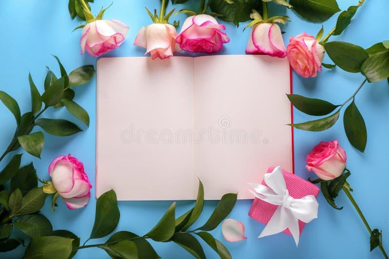 Bei rose e taccuino con le pagine in bianco sulla tavola di colore immagine stock