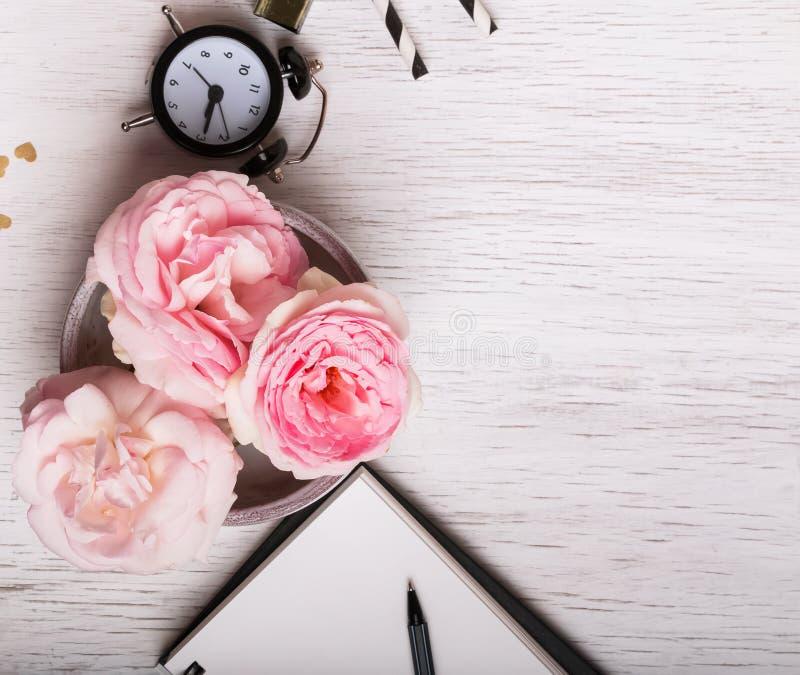 Bei rose ed orologio rosa sulla tavola bianca fotografie stock