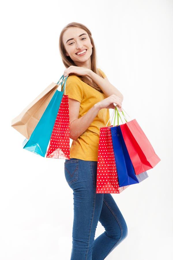 Bei sacchetti della spesa sorridenti della tenuta della giovane donna e stile casuale su fondo bianco Jeans e camicia gialla fotografie stock libere da diritti