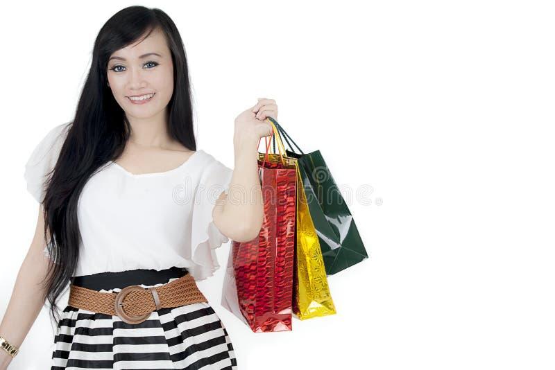 Bei sacchetti della spesa della tenuta della donna sullo studio immagine stock libera da diritti