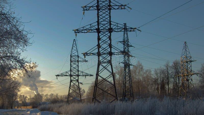 Bei Sonnenuntergang im Winter, Hochspannungsunterstützung lizenzfreies stockbild