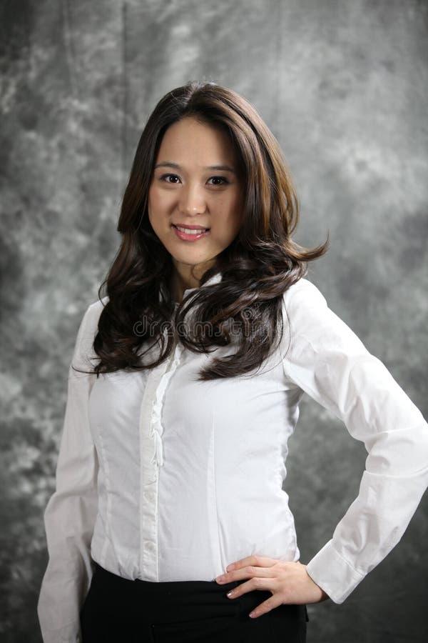 Bei sorrisi felici asiatici della donna di affari alla camma fotografia stock libera da diritti