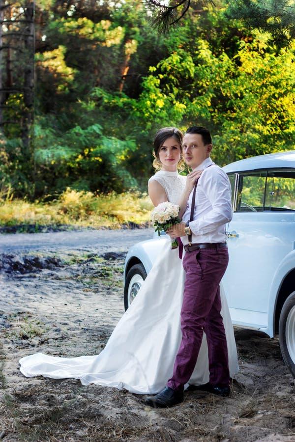 Bei sposa e sposo in belle attrezzature con un'automobile di nozze immagine stock