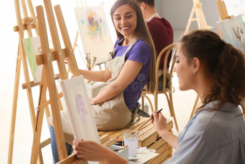 Bei studenti durante le classi a scuola dei pittori fotografia stock