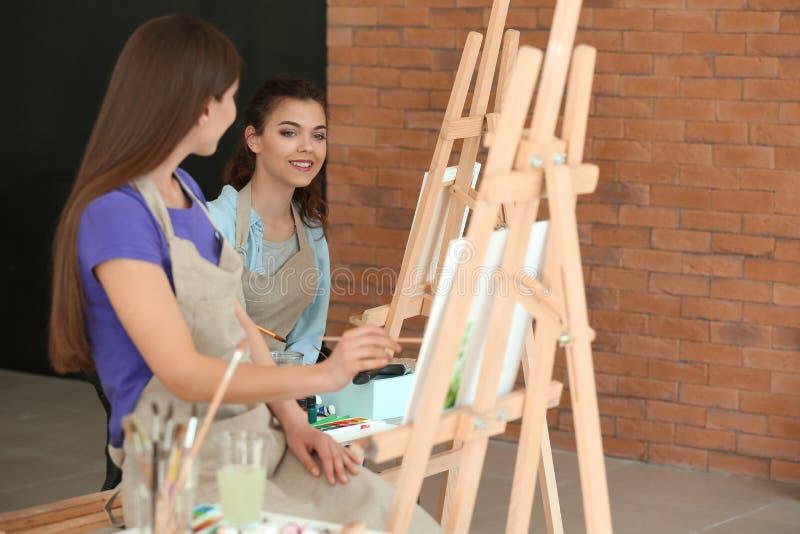 Bei studenti durante le classi a scuola dei pittori fotografie stock libere da diritti