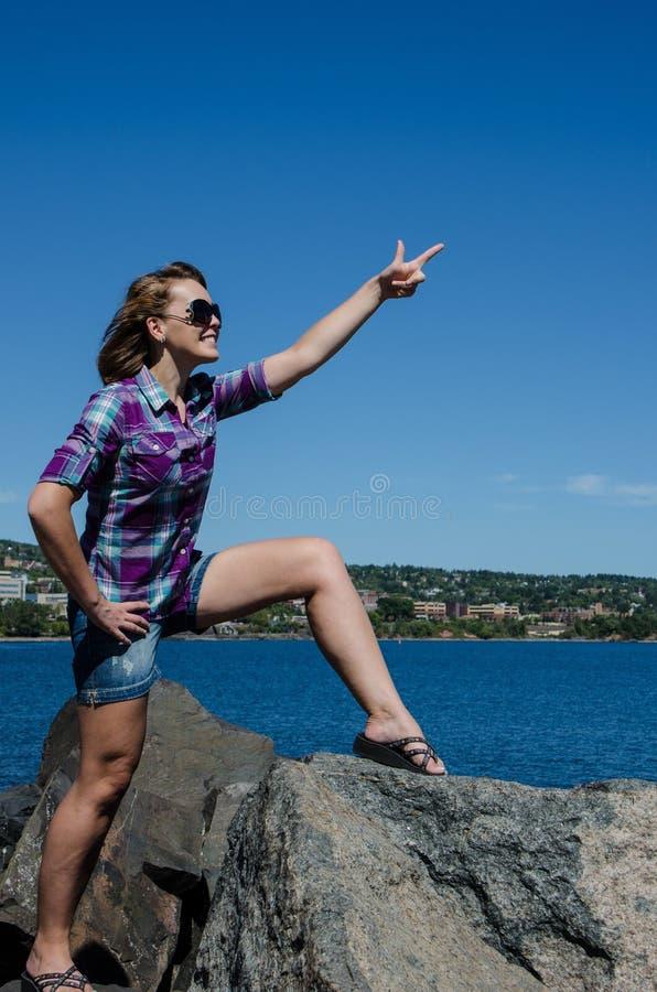 Bei supporti della donna adulta sopra le rocce con le armi fuori che indicano fotografia stock