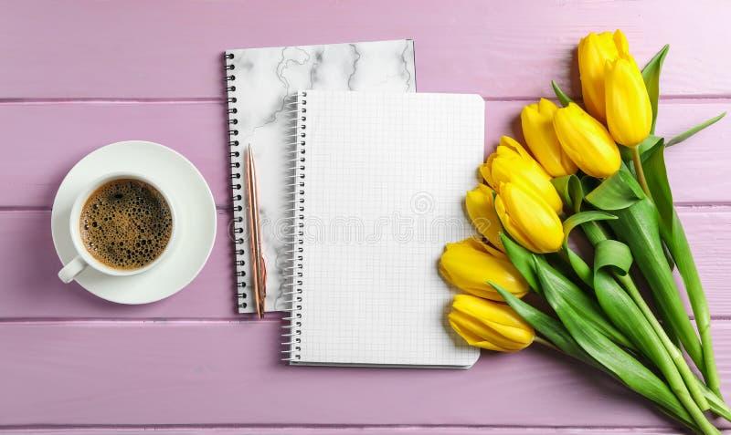 Bei tulipani, quaderni e tazza di caffè fotografie stock libere da diritti