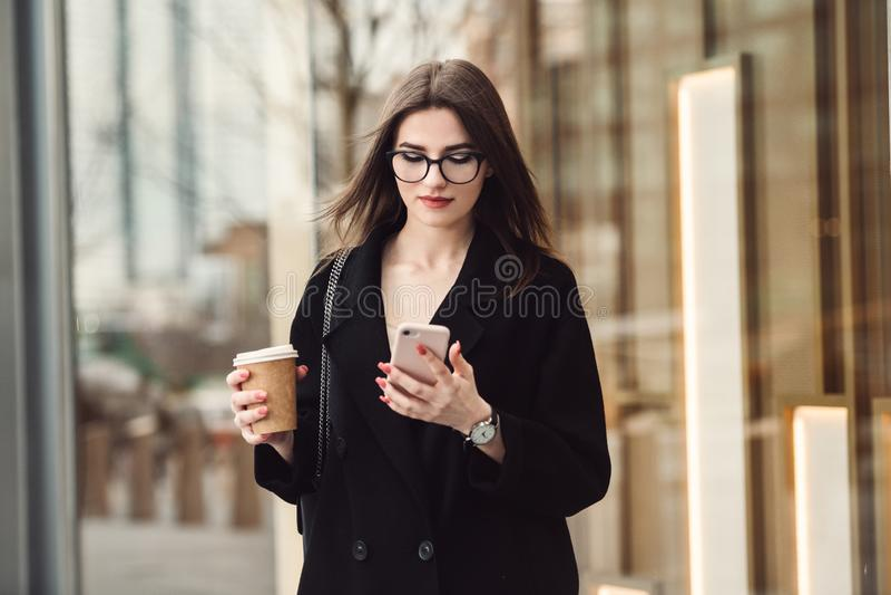 Bei vetri d'uso della donna di affari che camminano al lavoro con caffè e che mandano un sms sul telefono all'aperto fotografia stock libera da diritti