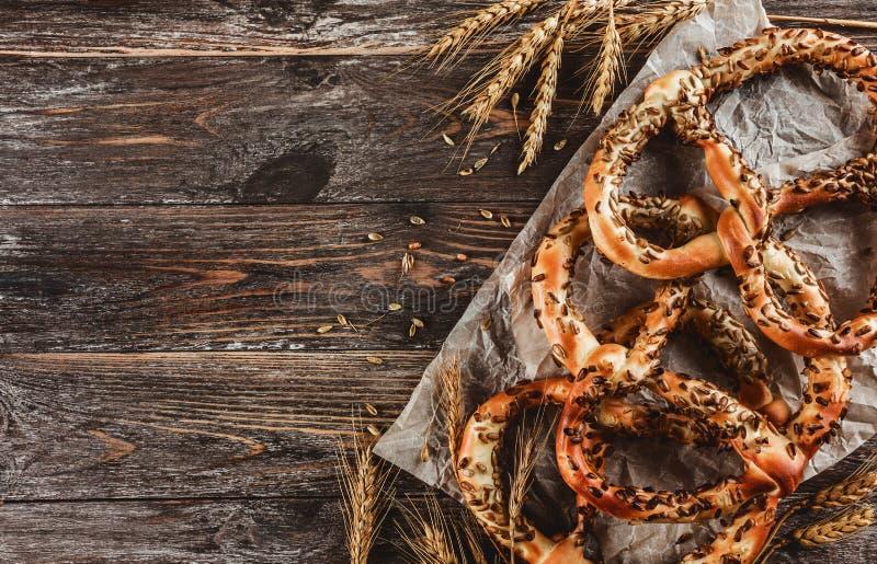 Beierse pretzels met met zonnebloemzaden, bruine houten achtergrond stock foto's