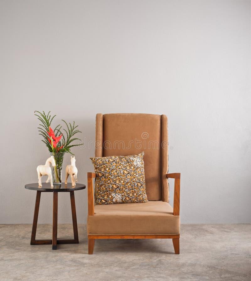 Beiga stoppad stol med sidotabellen royaltyfri foto